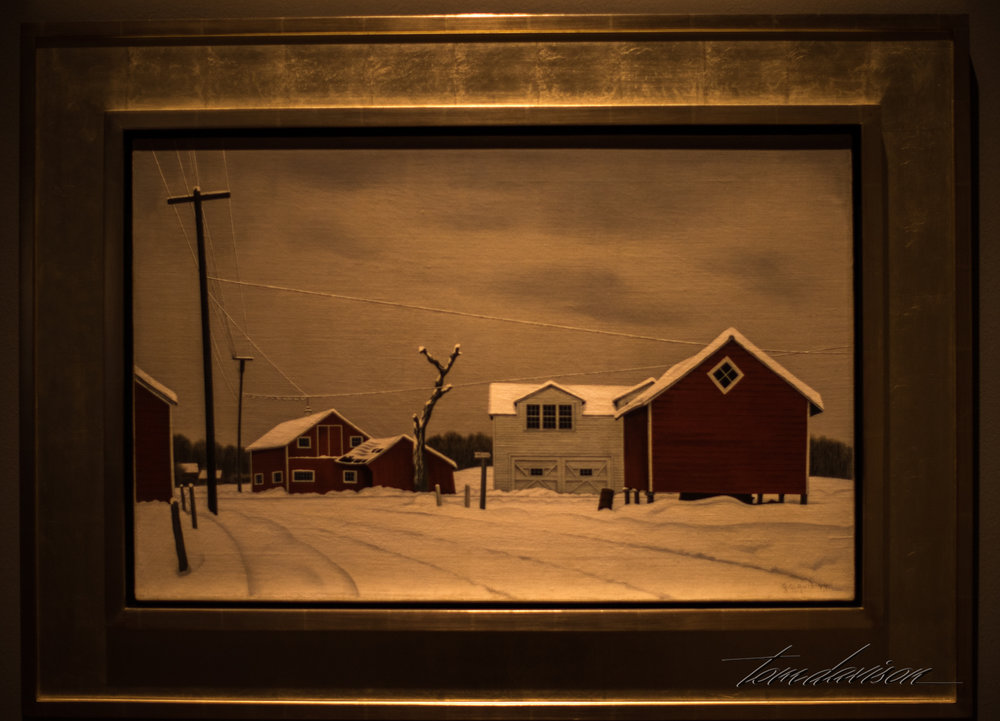 "This is a painting by George Copeland Ault (1891-1948).  It is an oil on canvas.  The information on the side tells the viewer, "" Daylight at Russel's Corners  expresses the melancholy and anxiety felt my many Americans following the Great Depression, which was further amplified by the Second World War.  The precise line and geometry in this work convey a sense of order.  The phone lines, frosted in ice, are the only connection to the outside world - potentially delivering chilling news from the war.  The quietness of the scene, coupled with the precise, hard-edge style, helps to make this image feel frozen in time."""
