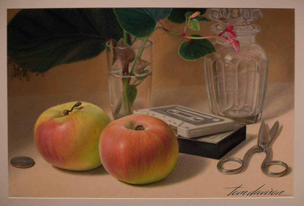 Mary Ann Currier painted this oil pastel on board entitled Carolina Apples.  She is known for using commonplace subjects in her contemporary still lifes.  In this painting she emphasizes the fleeting nature of existence by picturing music, food and other transient and sensual experiences.  The artist was born in 1927.  The painting was done in 1985.