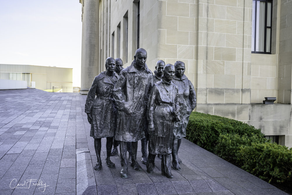 "This is George Segal's  Rush Hour , cast in 1995 of bronze.  ""This composition of anonymous figures evokes the deep isolation that can occur even when we are surrounded by others.  The bronze sculptures are made from casts formed by applying plaster-dipped gauze directly onto the faces and clothed bodies of the models, who were friends and neighbors of the artist.  Segal says that each figural form is a distinct psychological portrait.""  Segal was an American sculptor (1924-2000)."