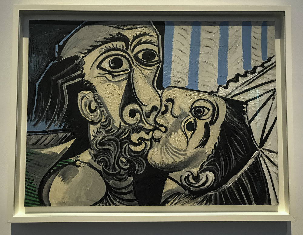 "The Kiss  , oil on canvas, 1969.  ""Locked together, two heads are joined by a single line that swirls around the entire canvas.  Out of two people, Picasso made one figure, reinforcing the intimate fusion that takes place in and ardent kiss.  He did not hesitate to reshape the faces to fit closely together, and he gave enough details to suggest this depicts the artist and his second wife, Jacqueline Roque.  Even in their tender embrace, both have their eyes wide open, as if sharing a revelation."""