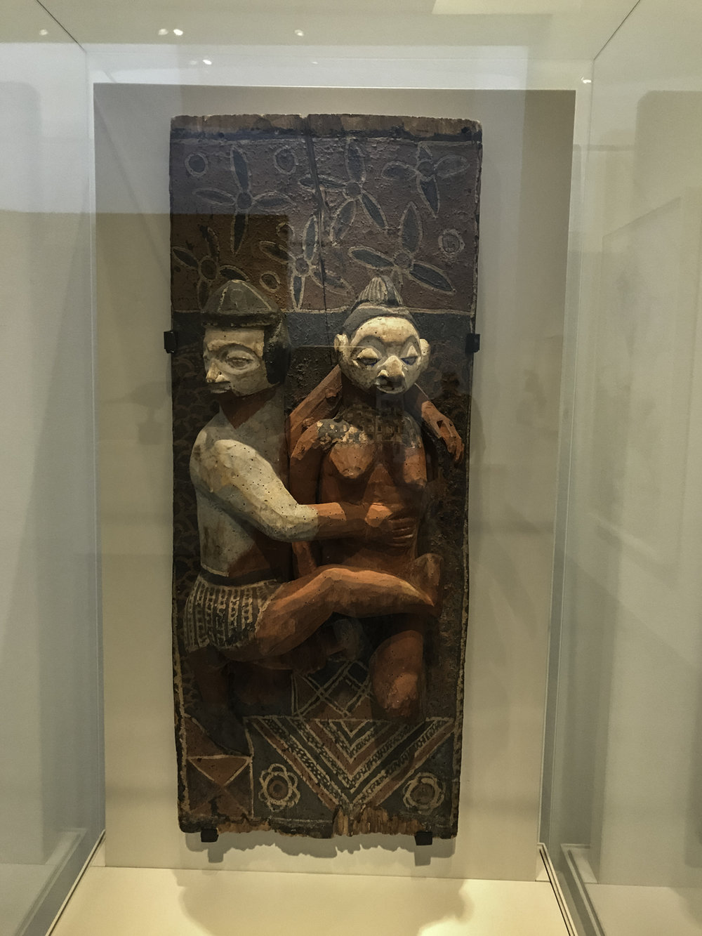"Panel,   wood with pigment, Nkanu culture.  This was another example in the exhibit which sought to show how other cultures influenced Picasso.  ""This panel shows a couple whose arms are entwined, yet they look in opposite directions.  Displayed in a restricted area, the young people who saw it learned about proper sexual behavior.  Although Picasso also depicted couples embracing, his works, in contrast, often have vivid and erotic intensity."""