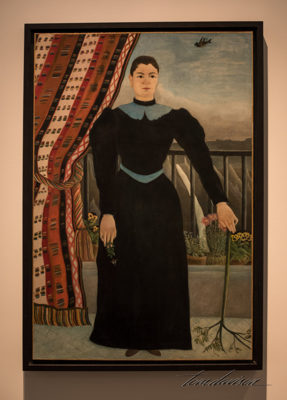 "Portrait of a Woman,   by Henry Rousseau (French), Oil on canvas, 1895.  ""In 1908, Picasso bought this painting by Henri Rousseau in a secondhand store for five francs.  He later called it 'one of the most truthful of all French psychological portraits.'  It breaks away from formal portraits of the time through a flattened image and odd touches, like an upside-down branch.  Picasso saw in Rousseau an authenticity and immediacy that he felt was absent in society.  He sought out Rousseau, a self-taught artist, and held a banquet in his honor.  It is considered one of the legendary parties of the early 1900s - full of farce, practical jokes, and dramatic personalitiese"""