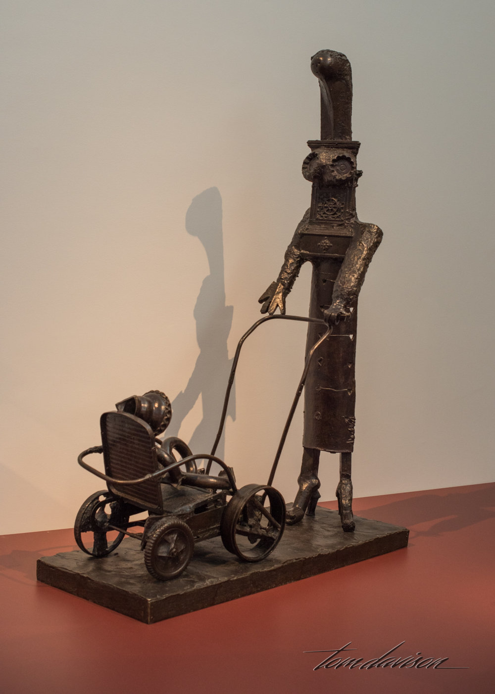 "Woman with Stroller,   Bronze, 1950. ""After seeing his lover Françoise Gilot push their son, Claude, in a carriage, Picasso began to construct this sculpture.  A master scavenger, he assembled it out of found materials before casting a bronze version.  Cake molds, stove plates, a table mat, rolled metal sheets, and pieces of pottery come together in this monument to motherhood."""