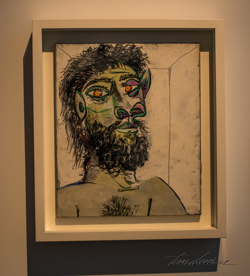 "Head of a Bearded Man,   Oil on Canvas, 1938. ""With dilated nostrils, spiked ears and thick bushy hair and beard, this man does no appear to be fully human.  He seems to be holding his volatile nature in check.  Sensing his own dark impulses led Picasso to create many striking portraits of men.  While this one is relatively tame, Picasso often went further, with machismo fantasies of himself as the Minotaur who chased and captured women."