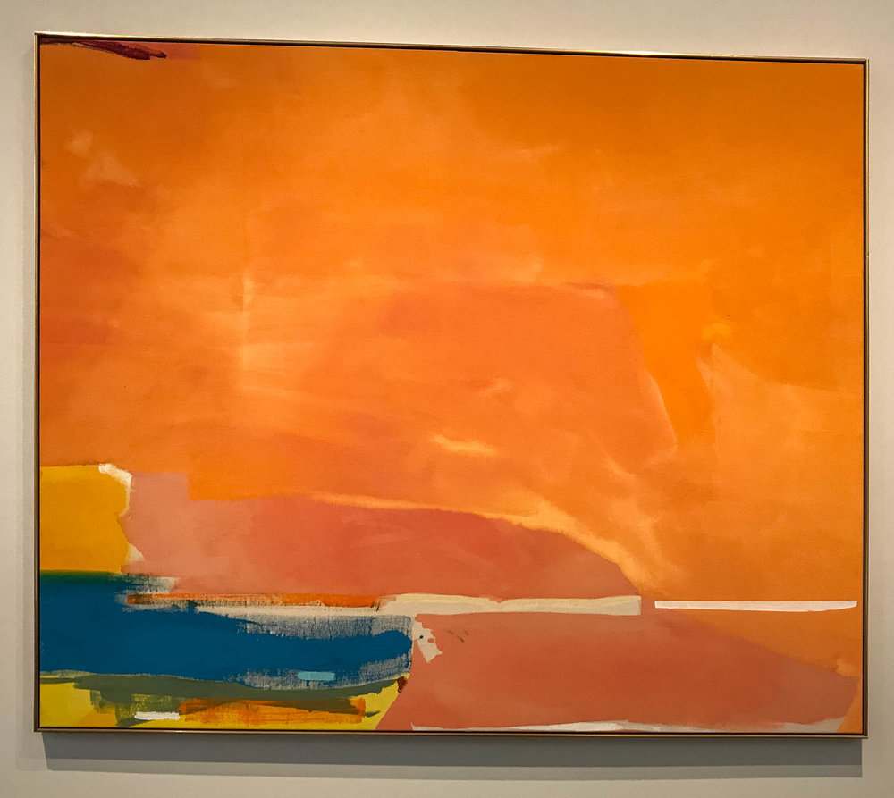 "Elberta , 1975, by Helen Frankenthaler (1928-2011), Acrylic on canvas.  ""To create  Elberta,  Helen Frankenthaler diluted paint to the consistency of watercolor and poured it directly onto raw canvas laid on the floor.  The result is a composition of sweeping planes of warm yellow, radiant orange and a contrasting highlight of vivid blue.  The narrow band running horizontally along the lower edge of the work is evocative of a horizon line.  This horizon-like band and the expansiveness of the composition give this lyrical painting the sense of an abstracted landscape.   Elberta 's forms and luminous hues make it a quintessential Color Field painting."""