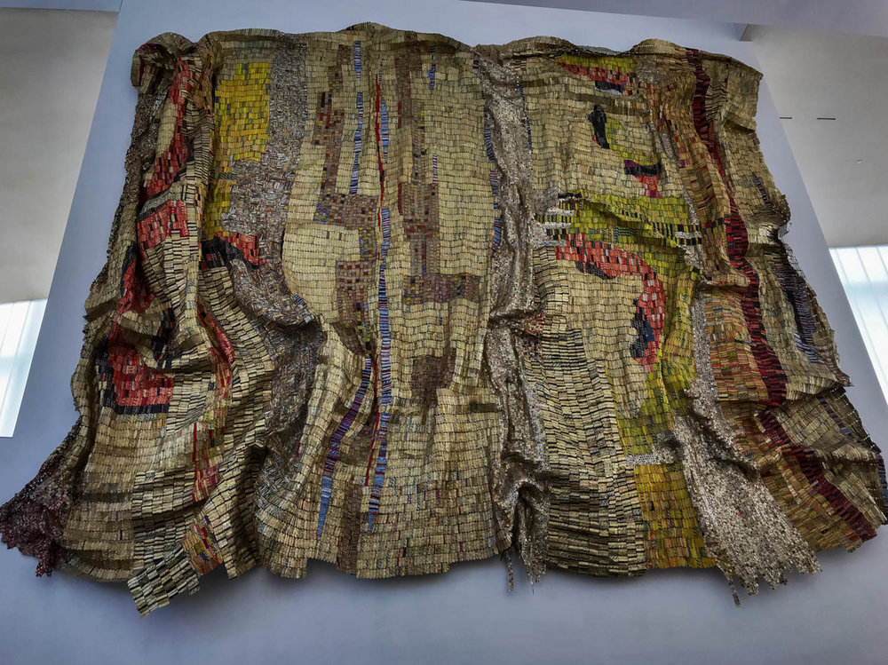 "Dusasa I , 2007 by El Anatsui (1944-) Found aluminum and copper wire.  This  very large wall hanging was one of the first art pieces that we saw after entering the Museum.  "" Dusasa I  was created from recycled liquor-bottle tops that have been flattened and stitched together using copper wire.  Working with the metal shapes, El Anatsui allows the material and colors to suggest the composition.  The artist's use of liquor-bottle tops acknowledges the historical role of liquor as a commodity traded by colonial powers for slaves and its ritual use as a libation, when it is poured as a form of prayer. . . The title  Dusasa  comes from Ewe words (people of Ghana), da and sass, meaning a fusion of disparate elements on a monumental scale.!"