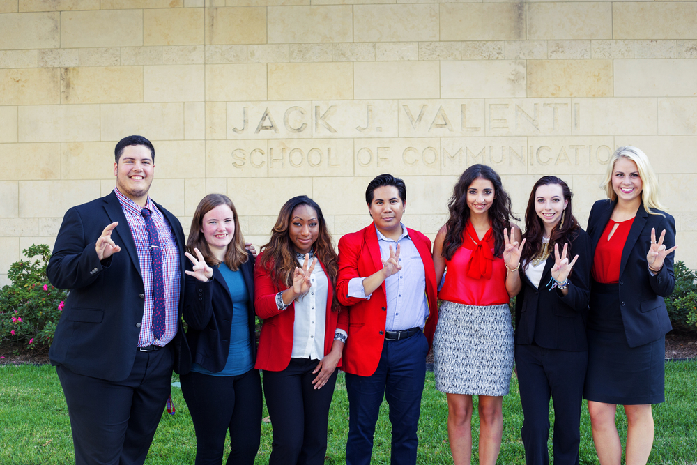 (L to R) Kevin Arevalo, Chancie Price, Alexis Culver, Gemrick Curtom, Christina Nemry, Caroline Alvarez and Angela Austin pose in front of the Jack J. School of Communication.