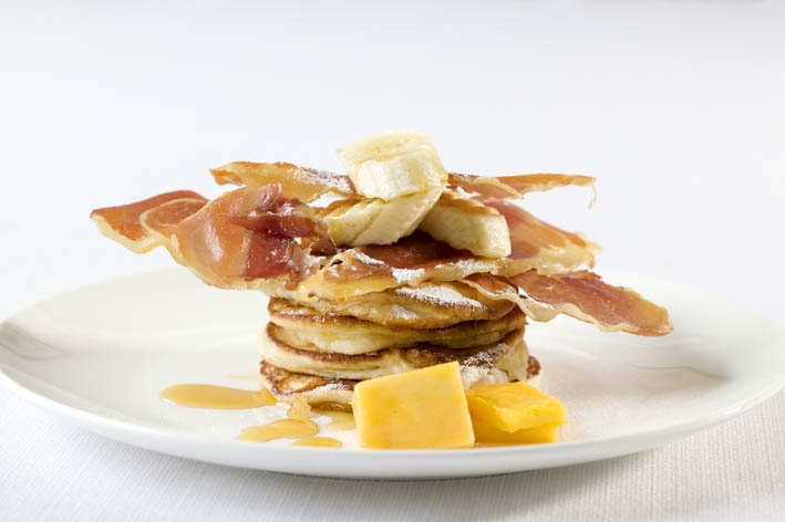 Crispy Pancetta on a bed of pancakes, topped with banana & syrup
