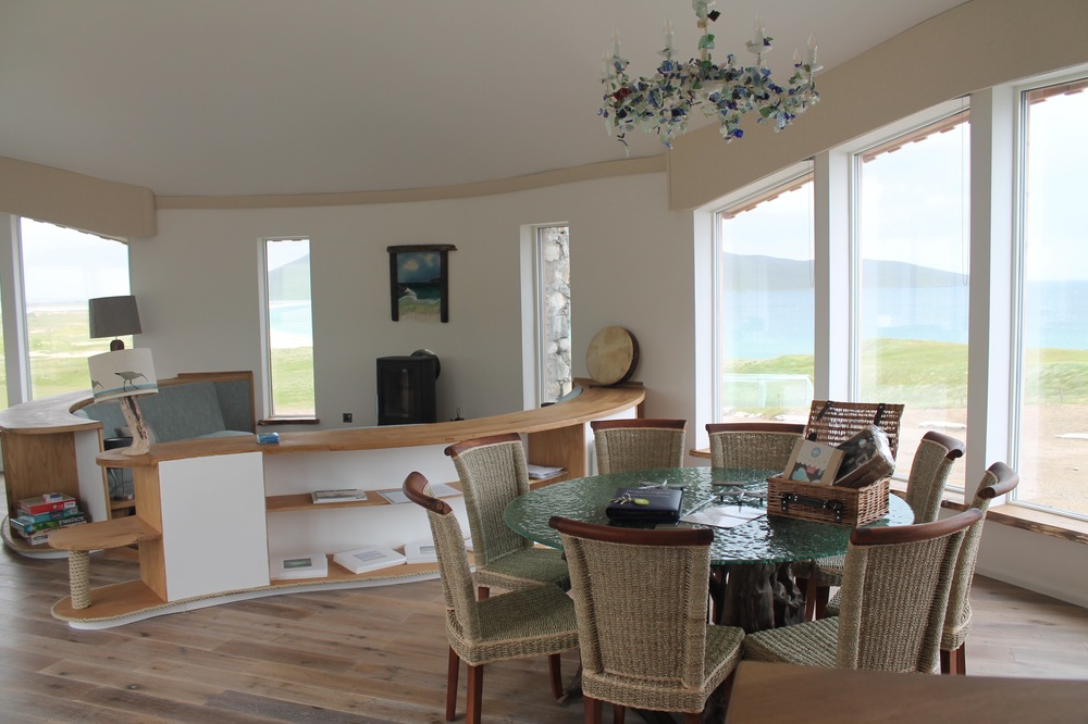 The glass dining table is set above a 1,000 year old wood base, giving the impression of viewing through the sea surface.  The views from the expansive living area are simply stunning