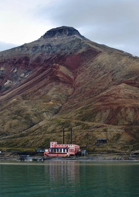 """Pyramidin näköinen vuori. Pyramiden, Huippuvuoret. """"Jäätikön vasemmalla puolella kohoaa vuori, jonka pyramidia muistuttavan huipun mukaan kaupunki on nimetty. Vuoren seinämää pitkin nousee katettu käytävä kohti maailman pohjoisimman kaivoksen suuta. Vuoren rinteeseen on muotoiltu valkoisista puunkappaleista sanat:Miru mir. Rauhaa maailmaan."""""""