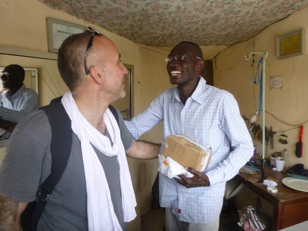 Bamba Cassé greeting Matthieu in his small workshop.