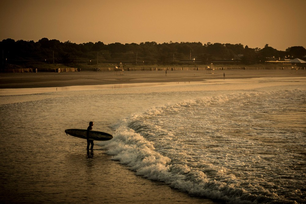 A surfer surveys the crashing waves before paddling out into the lineup for an early morning session in Narragansett, R.I.