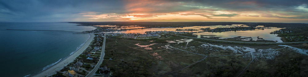 The sun drops to the horizon over the fishing village of Galilee, Rhode Island. This panorama is a composite image comprised of four separate images stitched together in the photo editing application Lightroom.