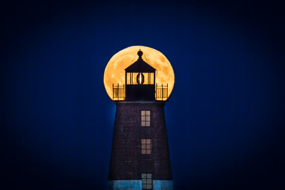 The 2016 Harvest Moon peers through Point Judith Lighthouse in Narragansett, Rhode Island.