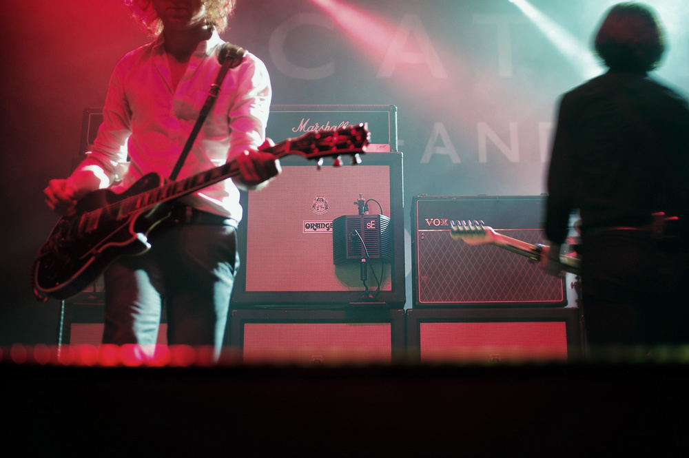 "One of three guitaRFs on stage, behind lead guitarist Johnny Bond (left) and singer Ryan ""Van"" McCann (right)."