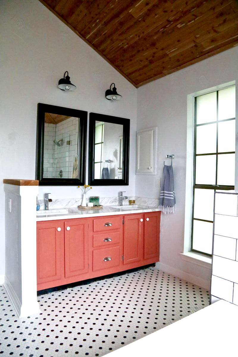 Love and Renovations  went bold by using a coral vanity in their master bathroom - a very fun choice for a room that many often keep pretty neutral.  I also love the classic tiled floor, the wood planked ceiling and the great window in the space.   Photo via Love and Renovations