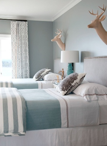 This room is pretty monochromatic with the icey blue walls and turquoise bedding.  The upholstered headboards and drapes really soften up the room and the faux deer heads provide a fun twist to a more traditional space.  Image:  Bear Hill Interiors