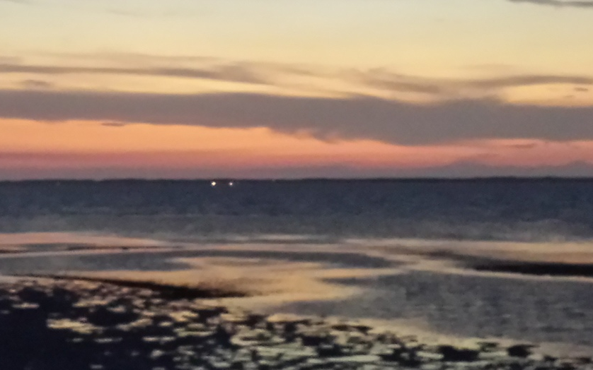 In the scene that the camera captured the horizon merged with the dark part of the bay.
