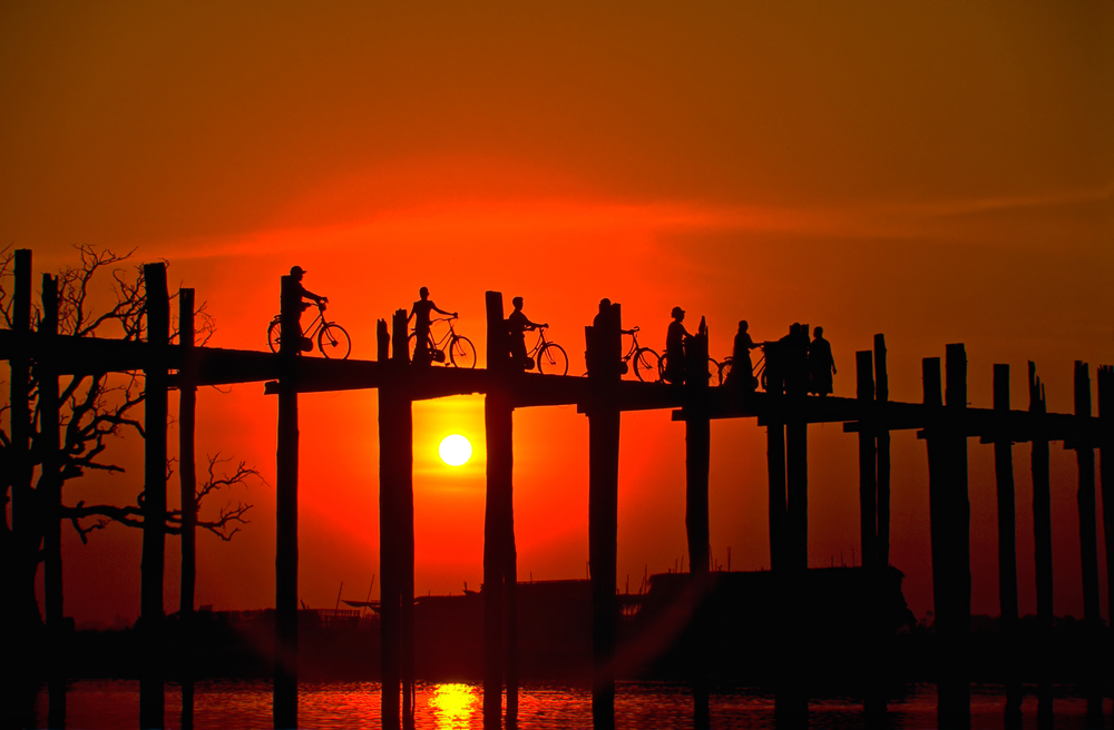 Bicyclists cross the two century old teak U Bein Bridge at sunset, Lake Taungthaman, Amarapura environs, Myanmar (Burma), Asia.