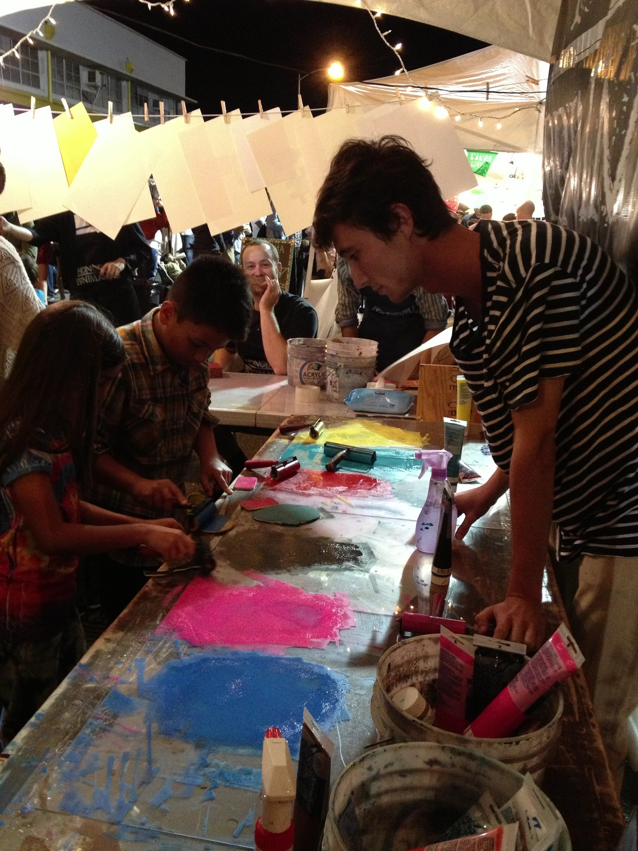 Joseph Nam, UH Manoa Printmaking student, presides over the ink slabs at a joint UH/HP relief print demo at Honolulu Night Market on 3/16/13.