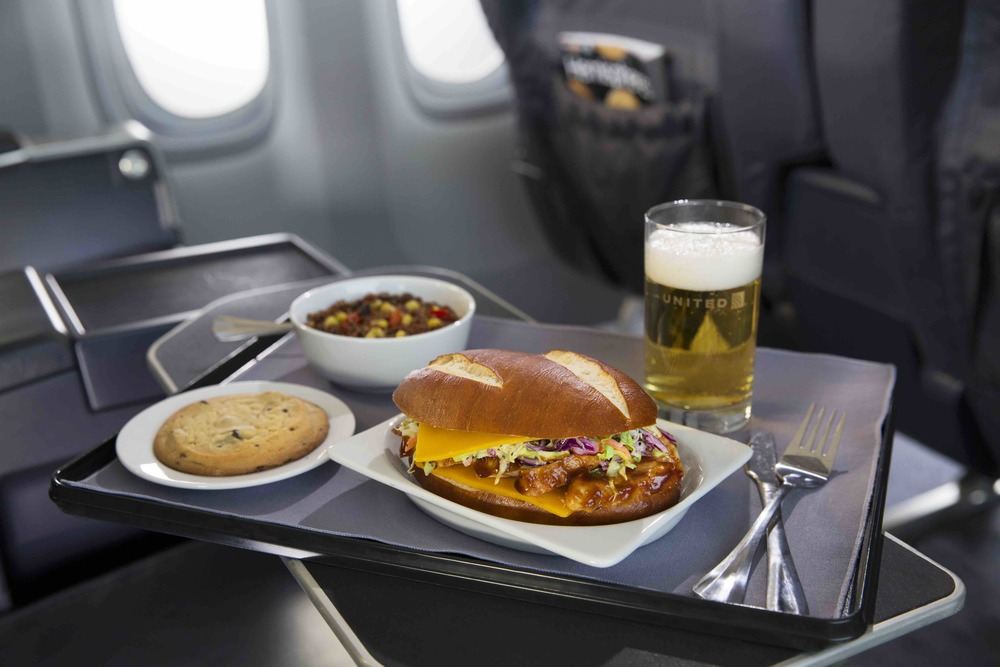 "United is improving food in first class on many regional jet flights. That's the ""Artisanal pretzel roll filled with tangy barbecue chicken and creamy coleslaw, paired with a tri-color quinoa side salad."" Photo: United Airlines."