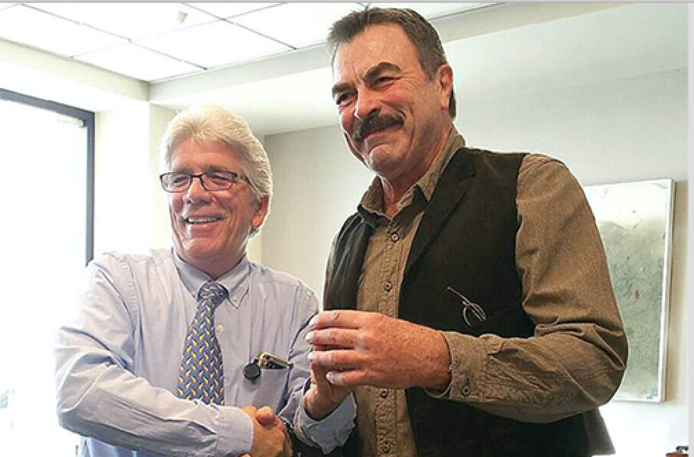 Tom Selleck receives his one-year of service pin from Jim Trabucco, a United customer service manager at LAX.