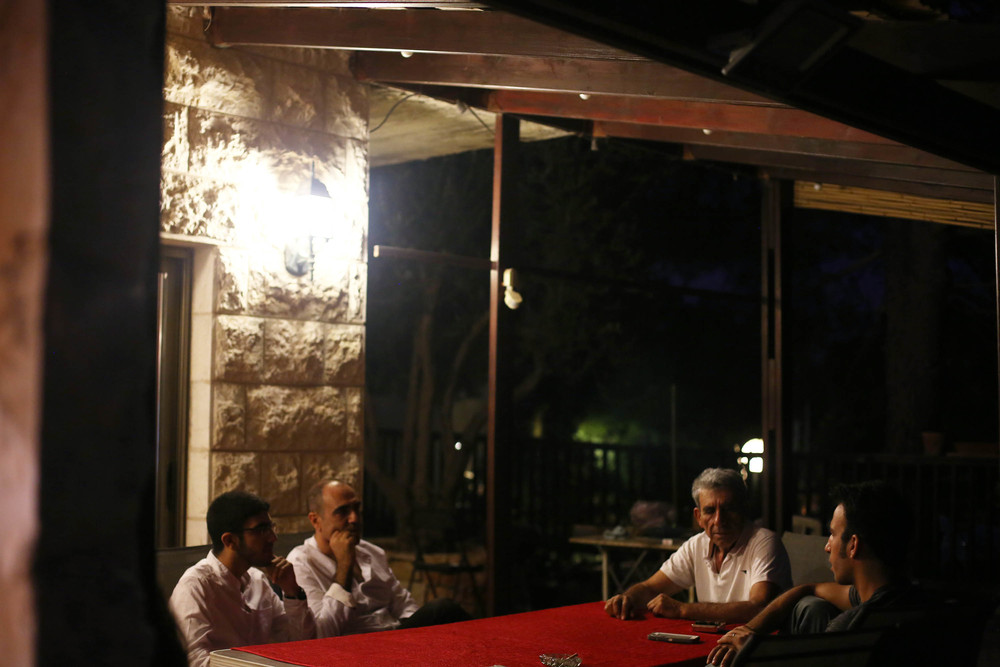 The men sit outside smoking and discussing politics while the table is being set.