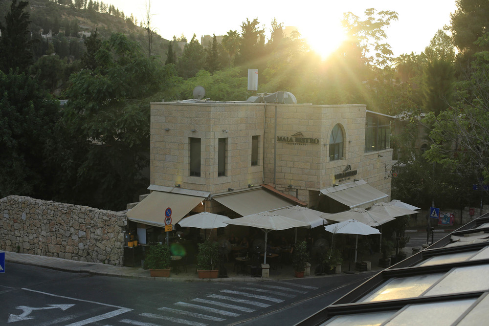 the sun sets behind a restaurant in Ein Karem