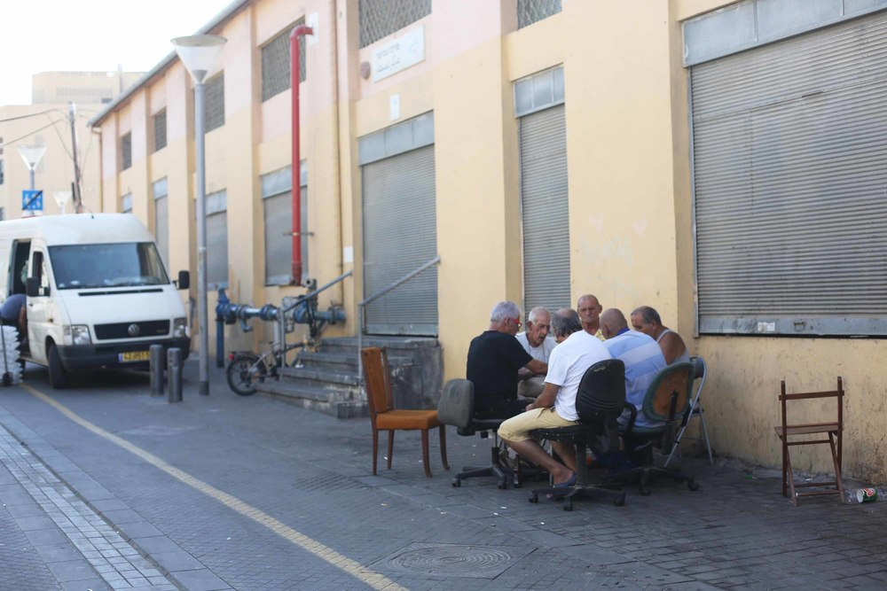 A classic image of men playing cards on the street.