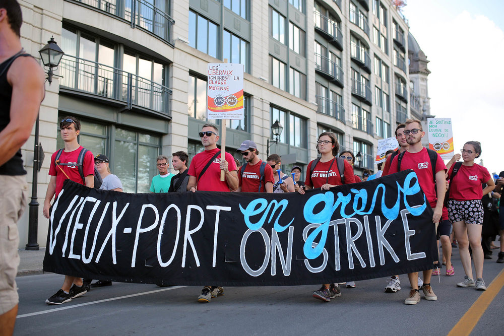 the staff at the old port were on strike. they peacefully marched along the street with a police escort.