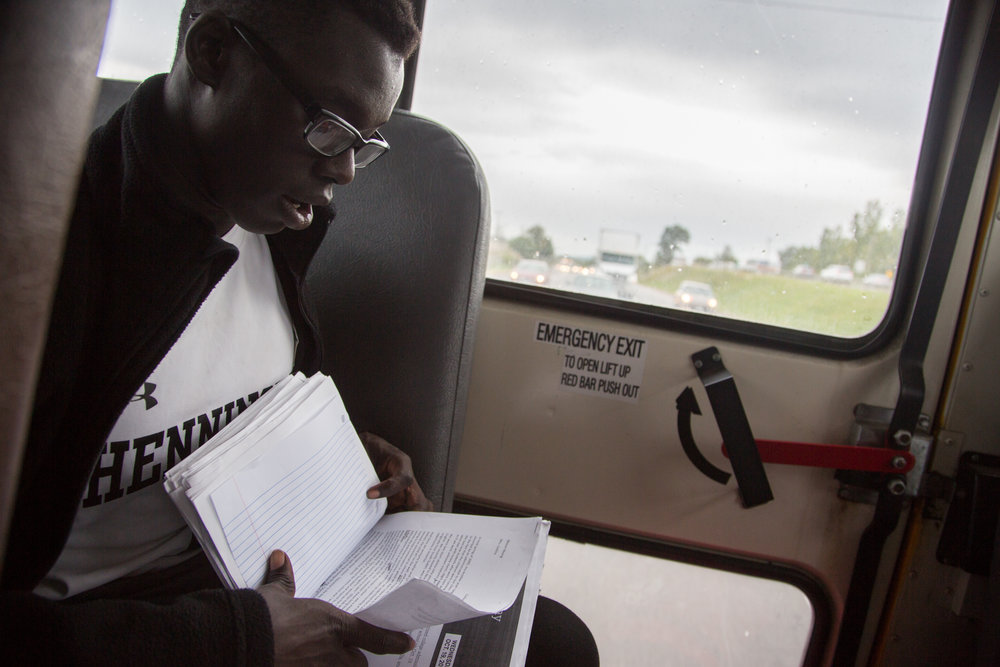 Neoan Nyang works on his homework assignment during the bus ride to Skaneateles. Most of the players try to balance school with their soccer games and practice.