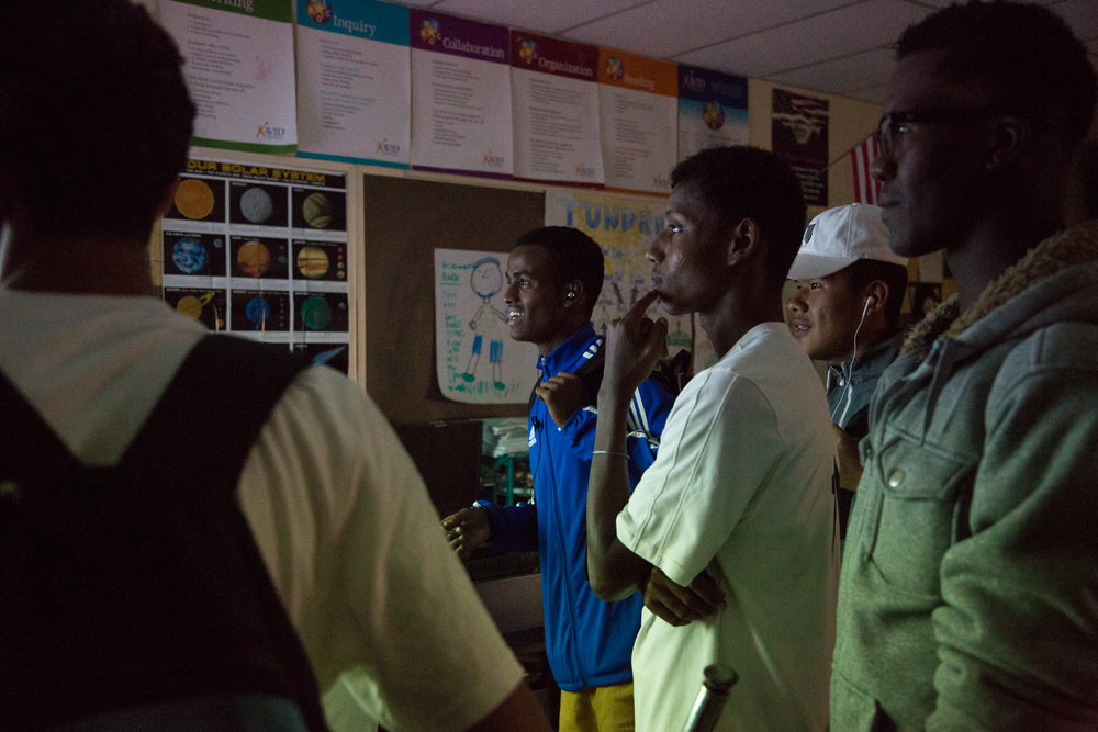 Ramadan Saad, AbdiRashid Abdi and other players watch a soccer game on a projector in the Science classroom at Henninger high school.