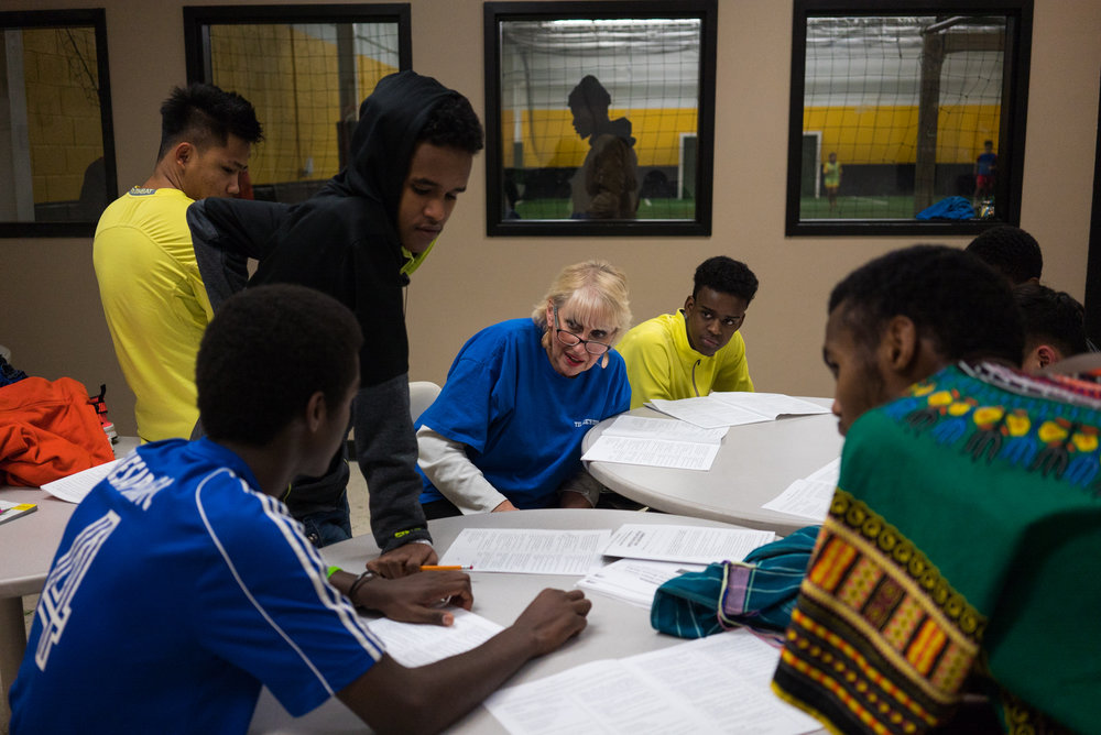Joyce Suslovic (c) teaches American history to a group of high school students who are mostly refugees resettled in Syracuse. Many high school kids come to play soccer at Tillie's touch, an organization that provides soccer facility/equipment to low income families in Syracuse. After Joyce came, many students joined her to study for the Regents examination.