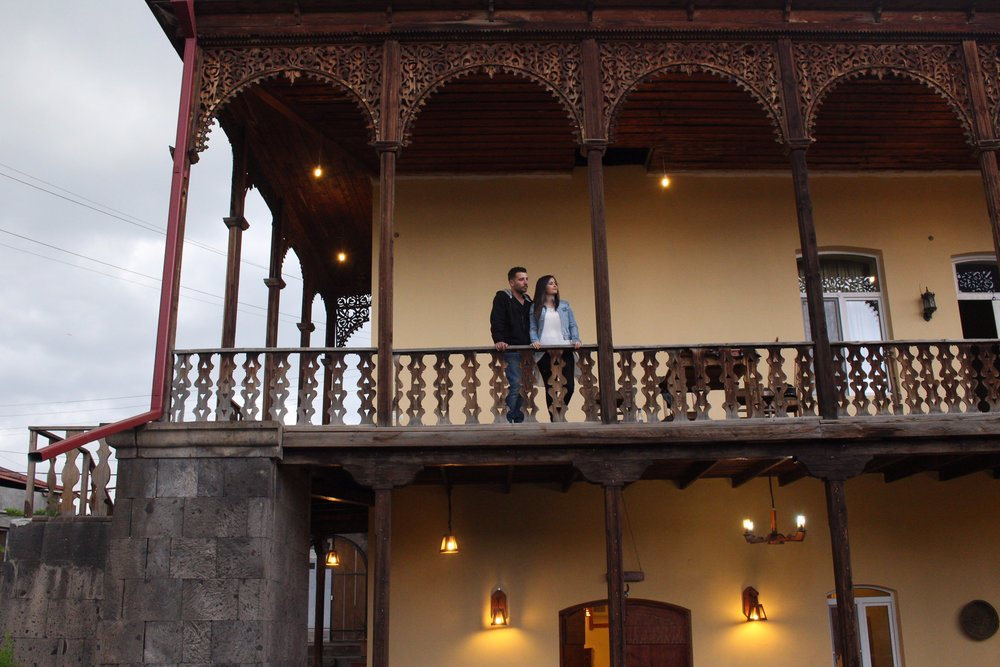 "Talar Zakarian(from Kamisli, Syria) and Hovik Aroyan(from Tartous, Syria)   standing in the balcony of ""Old Ashtarak"" restaurant, the building is also their home   Photo credit James Aram Elliot on assignment for the ARP, 2017."