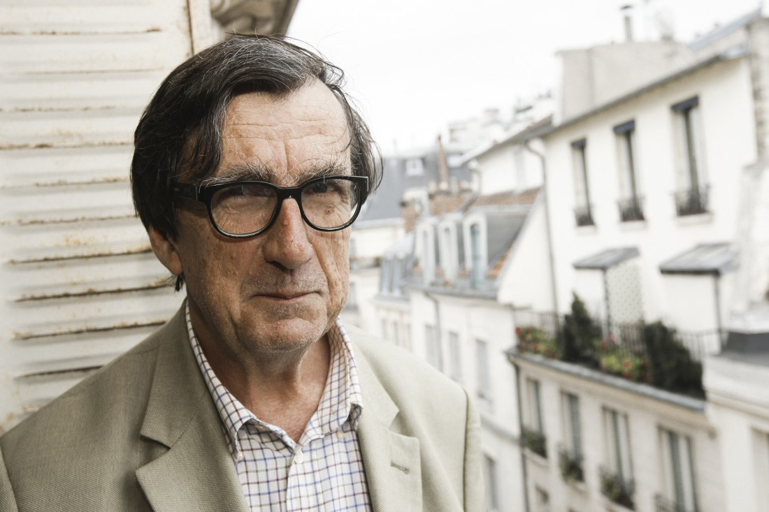 A photograph of Bruno Latour against an urban residential background