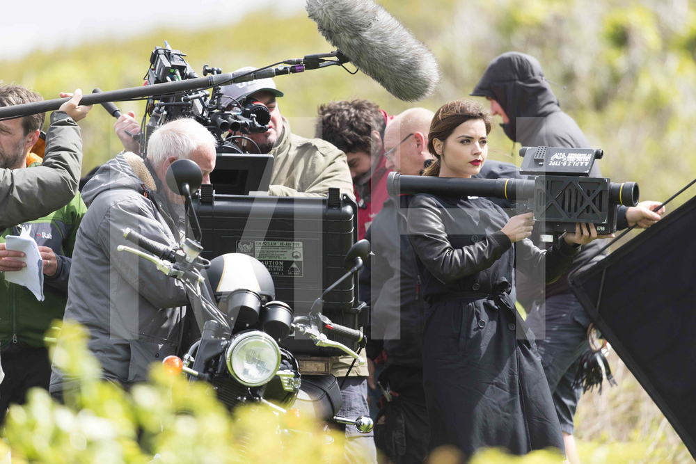 BARRY, WALES - MAY 18: The Doctor's companion Jenna Coleman who plays Clara Oswald is spotted holding a rocket launcher during filming for the ninth series of BBC show Doctor Who in grassland near Barry beach on May 18, 2015 in Barry, Wales. The beach was being used to film the aftermarth of a plane crash. (Photo by Matthew Horwood)