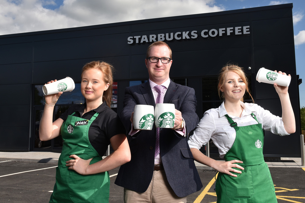 BRIDGEND, WALES - JULY 30: A new drive-through Starbucks is opening today (July 31) at Waterton Park, Bridgend. Picture shows Nick Golunski of Cooke & Arkwright with Alex Jones (left) and Cerys Lloyd (right). (Photo by Matthew Horwood)