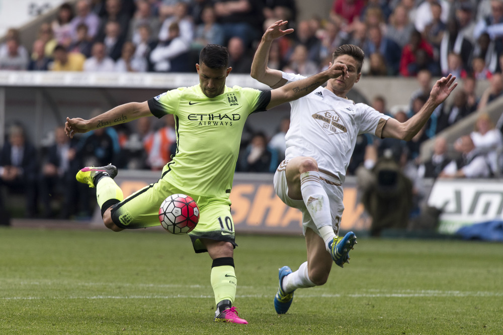 Swansea City v Manchester City Barclays Premier League match at the Liberty Stadium, Swansea. Picture shows Sergio Aguero of Manchester City having a shot on goal whileFederico Fernandez of Swansea City attempts a tackle. PIC Matthew Horwood © WALES NEWS SERVICE