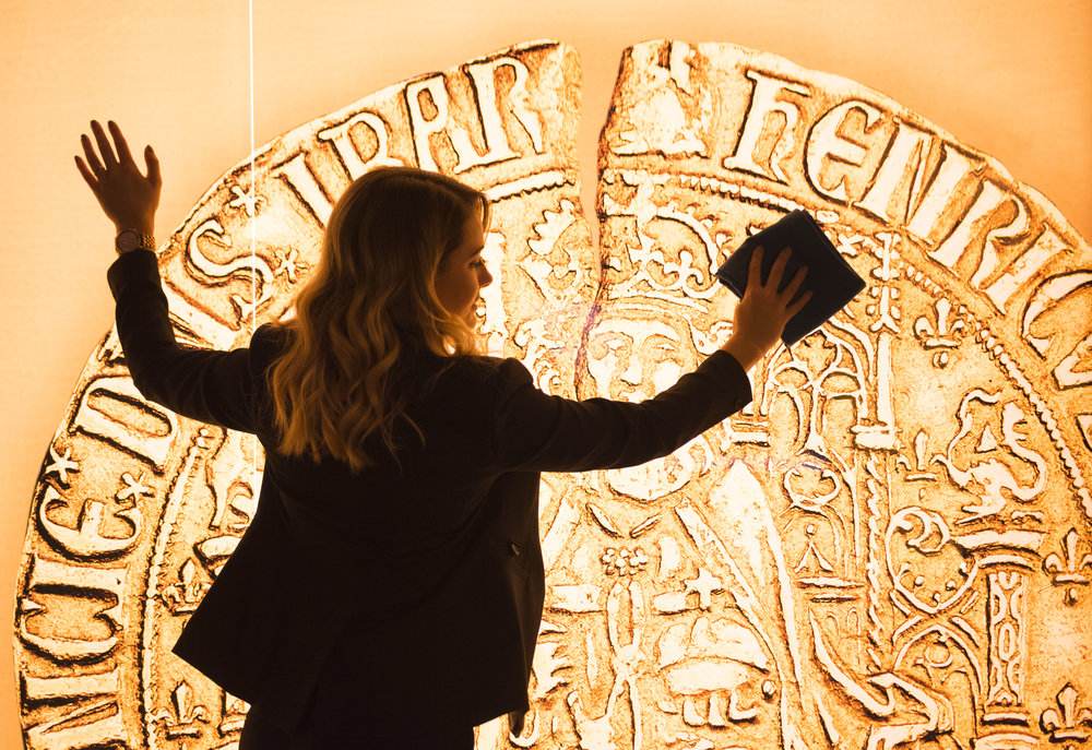 PONTYCLUN, WALES - MAY 17:  Sherry Thomas of the Royal Mint Experience cleans an image of a Henry VII sovereign coin during the opening of the Royal Mint Experience at the Royal Mint on May 17, 2016 in Pontyclun, Wales. The Royal Mint produces billions of coins a year for the UK.  (Photo by Matthew Horwood)