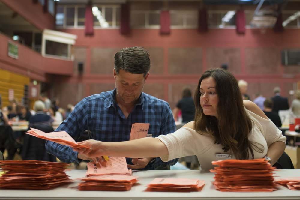 CARDIFF, UNITED KINGDOM - JUNE 09: A man and woman count ballot papers at the Sport Wales National Centre on June 9, 2017 in Cardiff, United Kingdom. After a snap election was called, the United Kingdom went to the polls yesterday following a closely fought election. The results from across the country are being counted and an overall result is expected in the early hours. (Photo by Matthew Horwood/Getty Images)