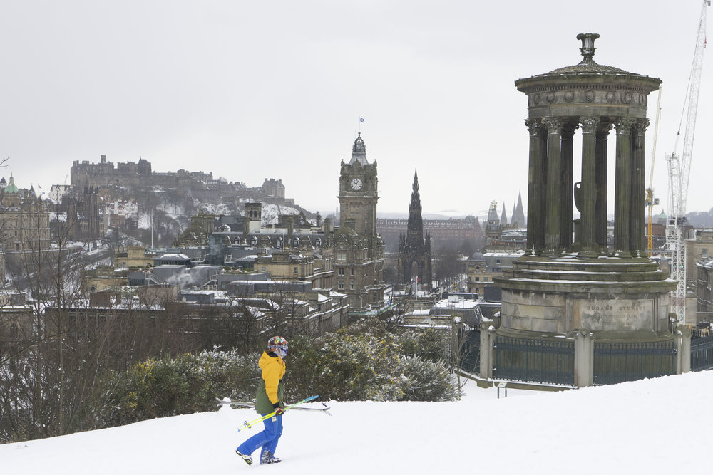 EDINBURGH, SCOTLAND - MARCH 1: A man with skis walks up Calton Hill which overlooks the city centre following heavy snowfall on March 1, 2018 in Edinburgh, United Kingdom. People have been warned not to make unnecessary journeys as the Met office issues a red weather be aware warning for parts of Wales and South West England following the one currently in place in Scotland. (Photo by Matthew Horwood/Getty Images)