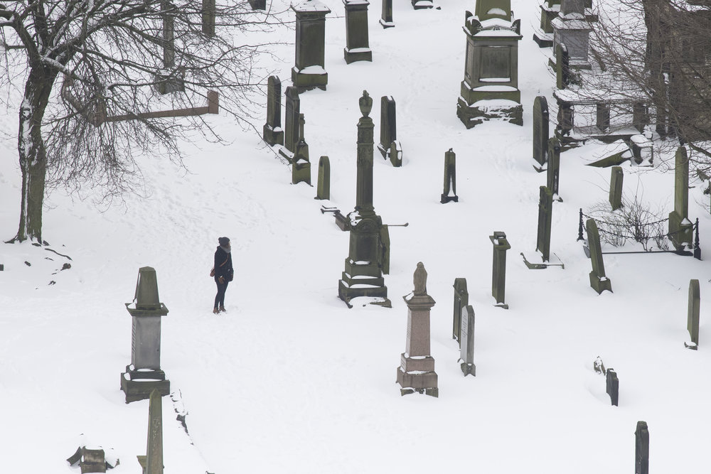 EDINBURGH, SCOTLAND - MARCH 1: A woman walks through a graveyard at Cannongate Kirk Church following heavy snowfall on March 1, 2018 in Edinburgh, United Kingdom. People have been warned not to make unnecessary journeys as the Met office issues a red weather be aware warning for parts of Wales and South West England following the one currently in place in Scotland. (Photo by Matthew Horwood/Getty Images)