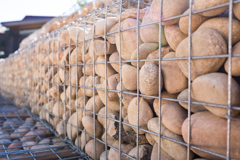 To create a Gabion Wall, cages are wired together into a shape and then filled in with rocks (or other materials). The particular wall we are installing at the Basalt Residence Project features a basket with a statue niche wired in. -