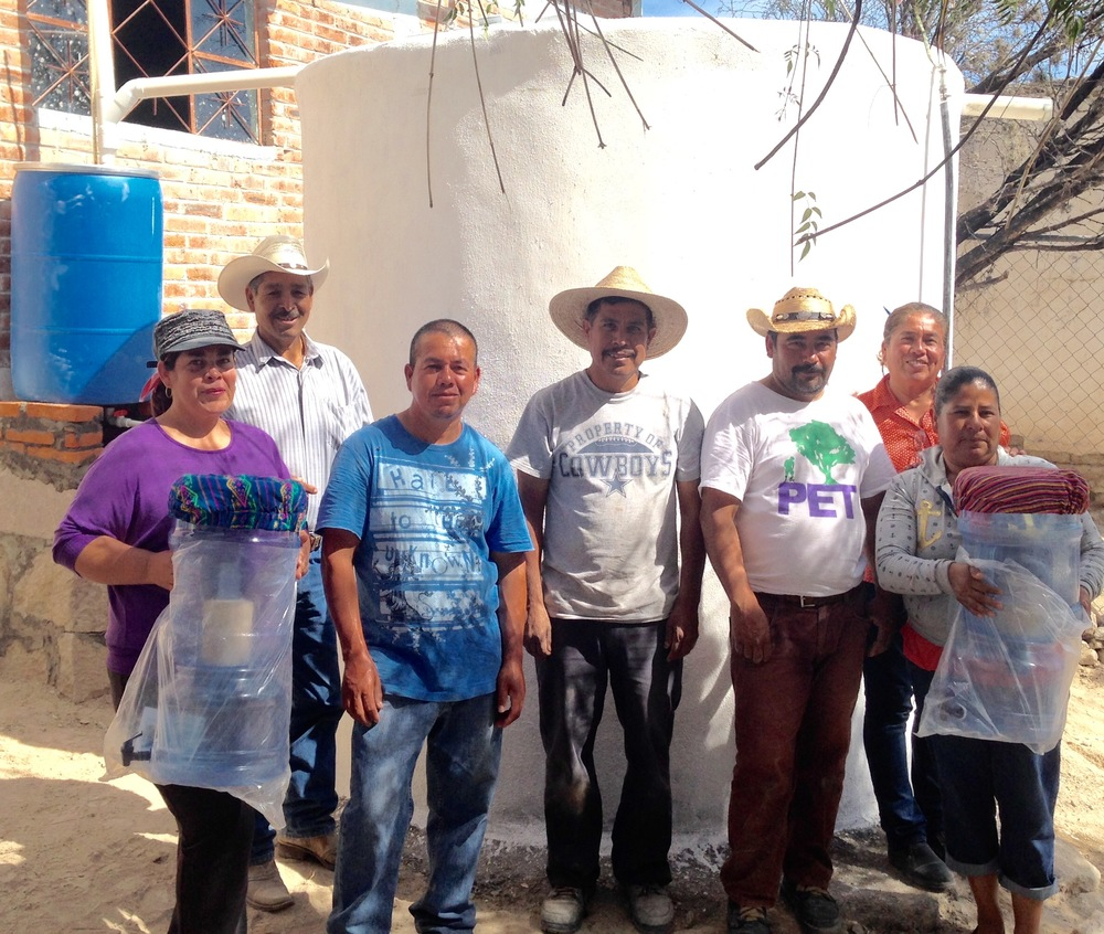 Community members of Pozo Ademado, some holding ceramic water filters, stand in front of their first rainwater harvesting system in November 2015.