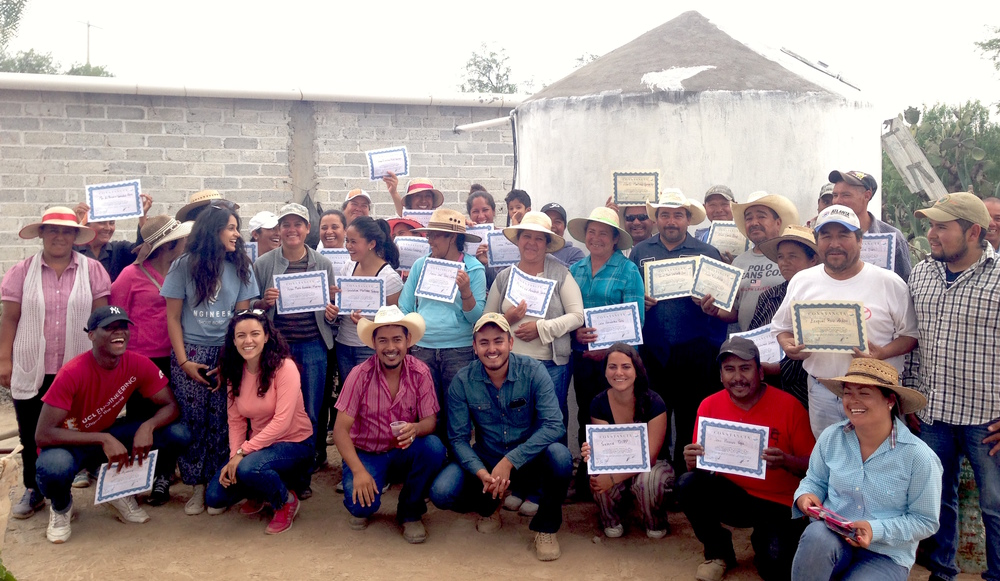 Members of EWB-UCL, Caminos de Agua, and San Antonio de Lourdes celebrate the completion of their first rainwater system together.
