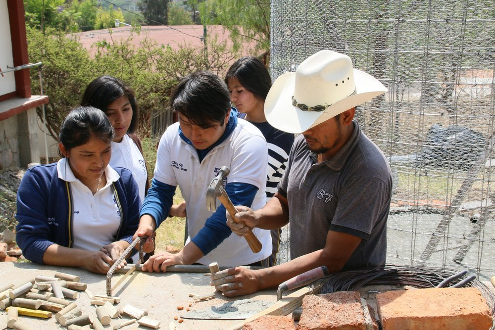 Saúl works with a group of students during the construction.