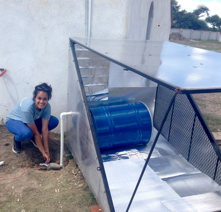 Dr. Adler's student, Ayisha Paw, primes the passive solar pump at Caminos de Agua for the first time.