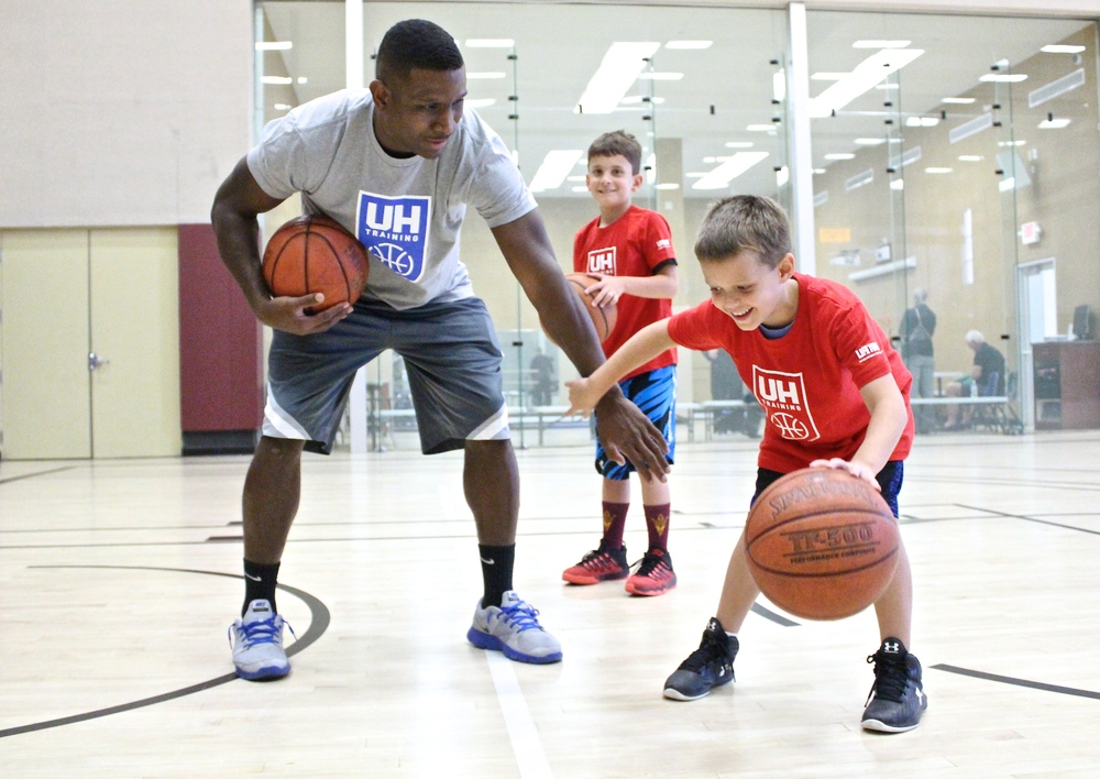 John McFall, Jr. protects his dribble from his trainer TJ. (photo by Donald Dangmuk)