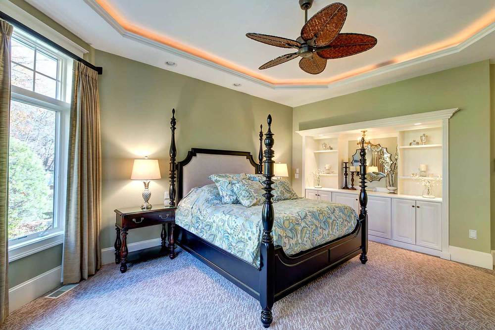 The bedroom contains a sculpted carpet, tropical ceiling fan, and mercury glass lamps.