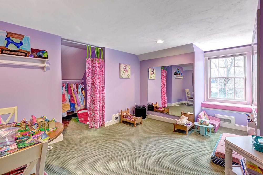 This children's playroom was transformed from an inlaw apartment. It has an art area and a full view mirror.